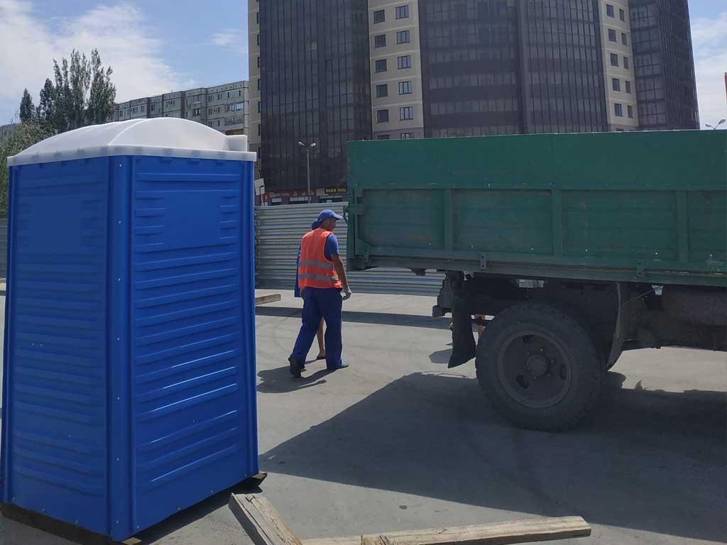 Строители рядом с туалетной кабинкой